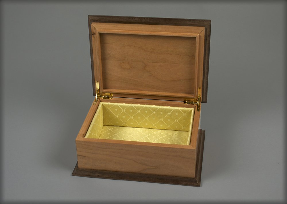 The interior of the box is lined with golden damask